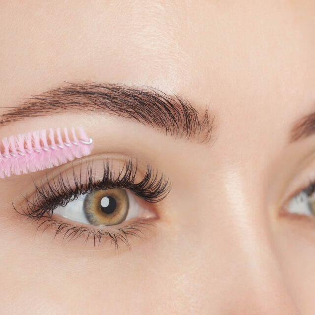 Beautiful Woman with long eyelashes in a beauty salon. Eyelash extension procedure. Cosmetology skin care